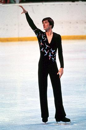 Спустя четыре года почти все фигуристы отошли от привычных рубашек и пиджаков, но британцы вновь оказались оригинальнее всех. На фото Робин Казинс, выигравший в 1980 году Олимпиаду, чемпионат Европы и ставший вторым на чемпионате мира. Расклешенные брюки, рубашка с большим вырезом и ярким принтом — Робин не только сильно катался, но и выглядел революционером.