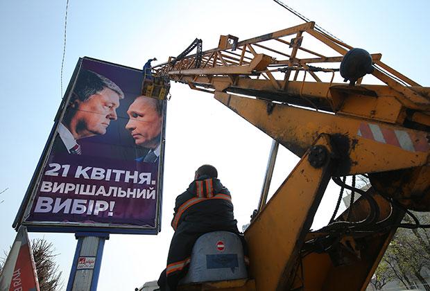 Рабочие монтируют агитационный плакат кандидата в президенты Украины Петра Порошенко на одной из улиц в Киеве