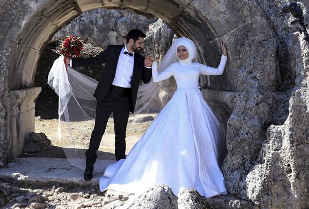 Молодожены Мерт и Зехра Хатемоглу позируют на фоне руин в Анталье. Жених одет по-европейски, а невеста выбрала классическое мусульманское платье.