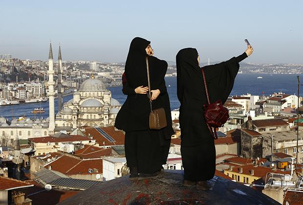 Молодые девушки, одетые в традиционные черные накидки абайи, позируют на фоне мечети на берегу Босфора в Стамбуле. В последние годы на улицах больших городов появляется все больше девушек в традиционной одежде.