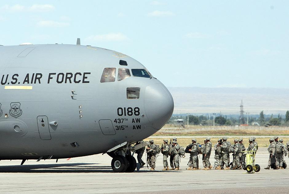 Американские военнослужащие садятся в самолет, направляющийся в Афганистан, в транзитном центре США в аэропорту Манас близ Бишкека, 23 июля 2010 года