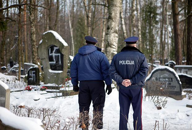 Офицеры полиции рассматривают оскверненные нацистской символикой могилы на Еврейском кладбище в Риге. Декабрь 2010 года