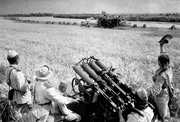 Колхозники убирают урожай под охраной зенитчиков, сентябрь 1943 года