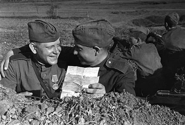 Солдаты в окопе читают письмо от родных