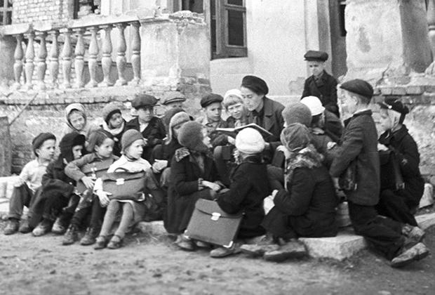 Урок на крыльце разрушенной немецкими обстрелами школы. Ленинград, 1943 год