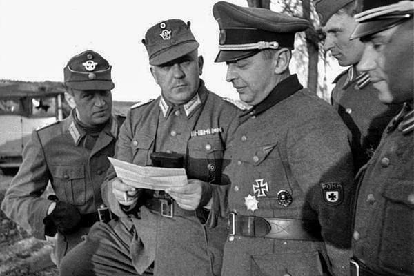 Бургомистр Локотского самоуправления Бронислав Каминский в окружении офицеров немецкой полиции (слева) и РОНА (справа)