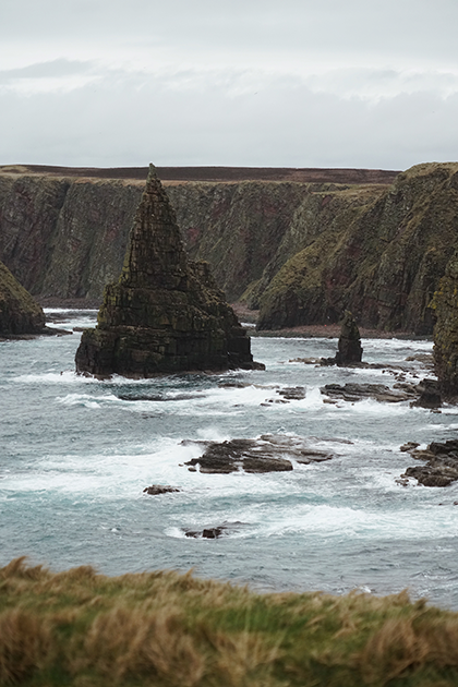 Если взглянуть на карту Шотландии и приглядеться к очертаниям ее побережья, создается впечатление, будто кто-то долго и небрежно рвал его на куски. Так же оно выглядит и в жизни. Самая северная точка материковой Шотландии Duncansby Head — яркий тому пример. Мрачные клифы, покрытые толстым ковром мха, и острые скалы, изборозжденные трещинами от суровых северных ветров, формируют эталонный шотландский пейзаж, притягивающий туристов со всего мира.
