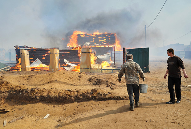 Добровольцы тушат лесной пожар, который из-за сильного ветра подобрался к жилым домам.