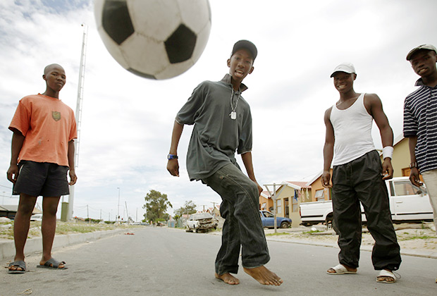 Молодежь играет в футбол на улицах района Хайелитш в Кейптауне