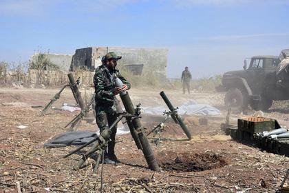 Солдат правительственных войск заряжает миномет