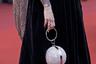 Гостья показа фильма Терренса Малика A Hidden Life («Тайная жизнь») появилась на красной дорожке с чрезвычайно популярным в этом сезоне шарообразным клатчем, покрытым стразами. Подобные модели выпускает марка Nazz.