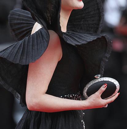 Гостья показа фильма «Мертвые не умирают» выбрала «роковой образ»: надела платье с плоеными «крыльями» по моде 1970-х и дополнила наряд черным овальным клатчем со стразами.