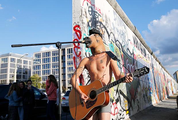Уличный музыкант у фрагмента Берлинской стены