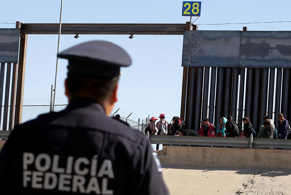 Мексиканский полицейский наблюдает за очередью мигрантов-просителей убежища