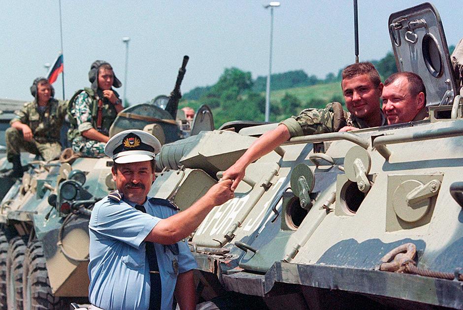 Сербский полицейский жмет руку российским миротворцам