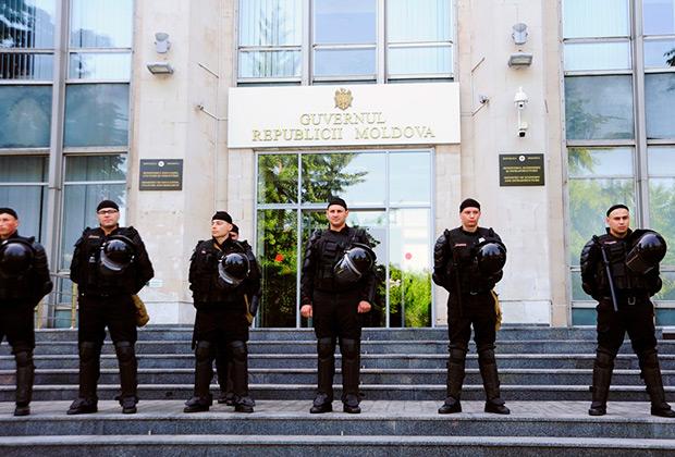 Сотрудники полиции в оцеплении на площади перед зданием правительства в Кишиневе, где прошел митиинг демократической партии Молдавии