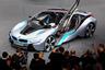 """Впервые BMW i8 <a href=""""https://www.bloomberg.com/news/articles/2015-01-30/the-bmw-i8-is-over-hyped-but-that-doesn-t-mean-it-s-not-great-review"""" target=""""_blank"""">был представлен</a> в сентябре 2013 года на Франкфуртском автосалоне. В модели используются два двигателя: электрический — мощностью 131 лошадиная сила и бензиновый, развивающий 231 силу. До 100 километров в час суперкар способен разогнаться за 4,4 секунды, максимальная скорость — 250 километров в час. <br></br> В 2018 году в линейке немецкой марки <a href=""""https://www.bloomberg.com/news/articles/2018-10-18/bmw-i8-roadster-review-the-practical-plug-in-hybrid-convertible"""" target=""""_blank"""">появилось</a> модернизированное купе и новый родстер. Совокупная мощность BMW i8 Coupe выросла с 362 до 374 лошадиных сил. На одной электротяге автомобиль сможет проехать 55 километров. BMW i8 Roadster оснащен той же силовой установкой, однако запас хода этой версии равен 53 километрам, а до 100 километров в час родстер разгоняется за 4,6 секунды. Начальная стоимость купе — около 150 тысяч долларов, родстера — порядка 175 тысяч."""