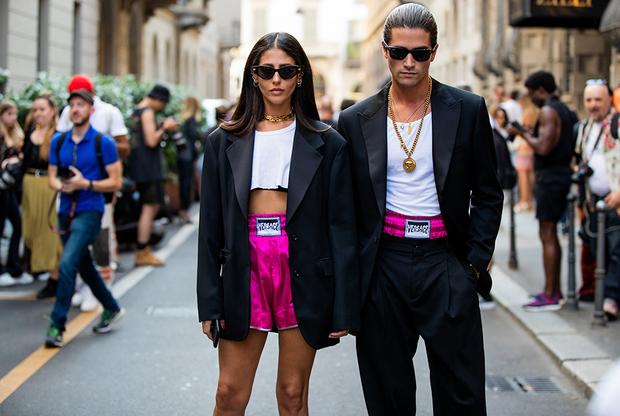 """Дизайнерка и блогерка-инфлюэнсерка Джильда Амбросио и модель Марк Форне выбрали «парный look» в рэперском стиле для визита на показ Versace: темные очки, смокинги, белые топы (у Джильды — очень короткий), боксерские трусы цвета фуксии (Форне приличия ради натянул сверху черные брюки, но резинку трусов выставил напоказ: <a href=""""https://lenta.ru/articles/2019/05/30/sagging/"""" target=""""_blank"""">сэггинг</a> на марше)."""