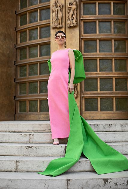 Элегантная гостья показа выбрала классический «футляр» нежно-розового цвета со светло-зеленым гипертрофированным бантом на спине от Elie Saab, а к нему — сандалии на шпильке, серьги-шандельеры и очки-«бабочки».