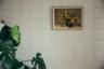Картина с подсолнухами — это, конечно, не конкурент пресловутому ковру, который висел на стене почти каждого советского дома, но тоже неплохо. Лучше только картина-чеканка с оленями или цветами. Массивное растение (у него говорящее название — «монстера») и выложенная белой плиткой стена скорее ассоциируются с поликлиникой, но ничуть не нарушают историческую обстановку.<br><br>«Нас вдохновили старые фотографии, хранившиеся здесь же, — пояснил Линас. — На них квартира была запечатлена непосредственно после распада СССР. Так что мы все оформили сами».