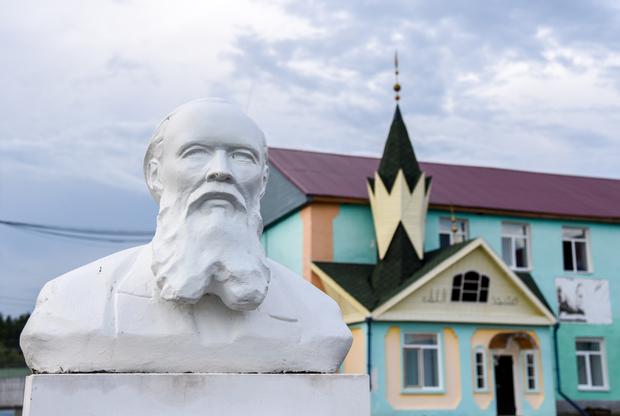 Территорию ЛИУ №19 украшает бюст Достоевского, установленный заключенным. Позади виднеется надомная мечеть, слева от нее — не попавший в кадр магазин, а еще левее — православный храм.