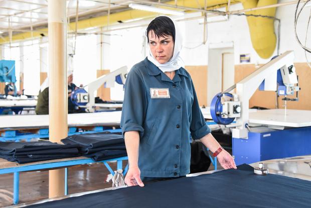 Закройный цех, входящий в состав швейного производства. Женщины фотографируются неохотно, у них много работы. Трудятся по восемь часов в день с перерывом на обед — как и положено по Трудовому кодексу (ТК).