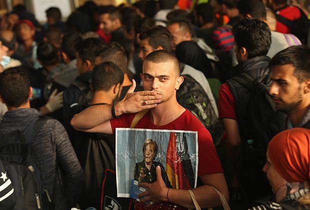 Мигрант из Сирии с портретом Меркель в 2015 году