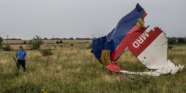 GRABOVKA, UKRAINE - JULY 18:  A Ukrainian police officer searches for human remains found in a field on July 18, 2014 in Grabovka, Ukraine. Malaysia Airlines flight MH17 travelling from Amsterdam to Kuala Lumpur crashed yesterday on the Ukraine/Russia border near the town of Shaktersk. The Boeing 777 was carrying 298 people including crew members, the majority of the passengers being Dutch nationals, believed to be at least 173, 44 Malaysians, 27 Australians, 12 Indonesians and 9 Britons. It has been speculated that the passenger aircraft was shot down by a surface to air missile by warring factions in the region.  (Photo by Brendan Hoffman/Getty Images)