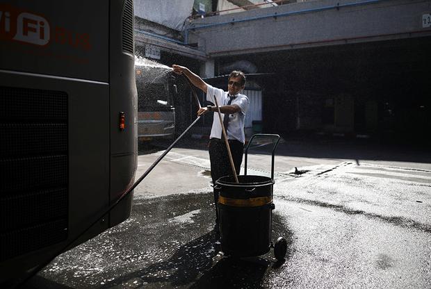 Водитель автобуса (как положено служащему транспортной компании, одетый в униформу — рубашку и галстук, хотя даже бизнесмены в Израиле обычно обходятся без галстуков) моет свою машину. Обычно в Израиле стоит сухая солнечная погода. Исключение — несколько недель в декабре и январе, когда нередки сильные дожди. Но сильнее всего машины и автобусы загрязняются во время хамсина — песчаной бури. На поверхности авто оседает тончайший слой песочной взвеси, напоминающей пудру.