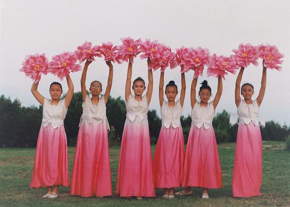 Девочки в традиционных китайских вечерних платьях готовятся выступить с танцем в честь региональных властей.