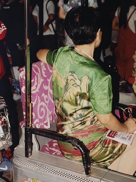 Женщина в общественном транспорте одета в платье с особым рисунком — репринтом картины классического китайского пейзажа.