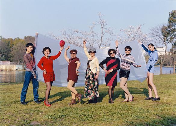 Группа китайских дам позирует для фото, в то время как два молодых человека держат ткань для фона. Снимок сделан в парке в Шанхае.