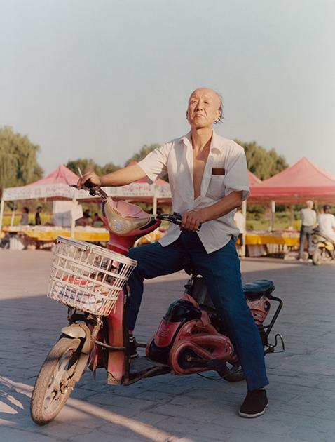 Пожилой китаец за рулем электромотоцикла. Снимок сделан в Пинъяо, единственном средневековом городе Китая, полностью сохранившем свой исторический архитектурный облик. У китайцев популярны велосипеды, мопеды, скутеры и мотоциклы. Обладатели разных транспортных средств зачастую передвигаются вместе с автомобилями по проезжей части, а не по выделенным дорожкам.