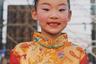 Девочка в традиционном китайском костюме улыбается на камеру. Впереди у нее танцевальное выступление на мероприятии в честь местных властей. Для образа ей зачесали волосы в пучок, нанесли румяна и покрасили брови. В современном Китае красота основана на европейских стандартах: белая кожа, стройное телосложение и высокий рост.