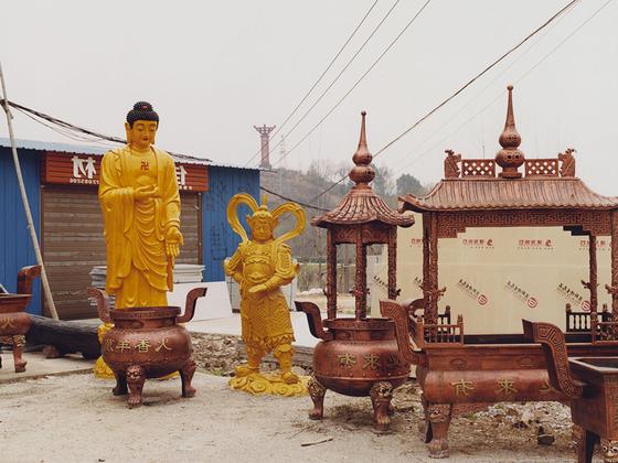 Снимок сделан в родном городке фотографа — Иньцзу (Yinzu). Он известен тем, что производит копии антиквариата, который затем продают в других городах Китая. Среди таких произведений искусства и статуи Будды. «Антиквариатом» украшают дома и заведения для улучшения имиджа или привлечения туристов.