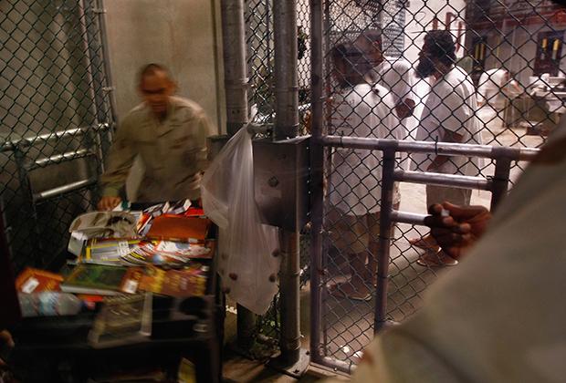 Тюремный охранник приносит книги заключенным