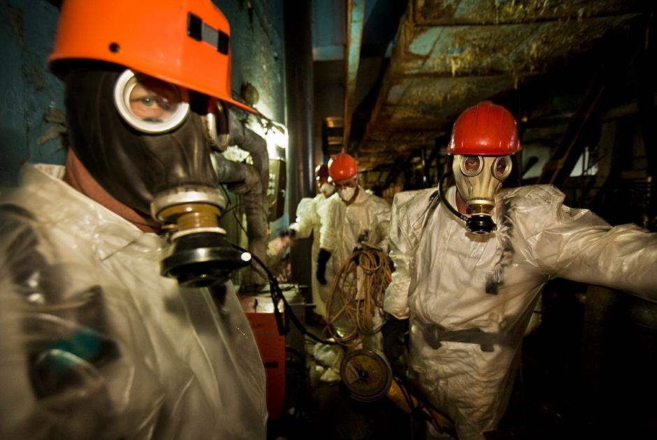 Рабочие в респираторах и защитных комбинезонах направляются бурить отверстия для опорных балок «Нового безопасного конфайнмента» (НБК) — защитной оболочки над четвертым энергоблоком, которая накроет устаревшее «Укрытие». Это опасная работа: уровень радиации настолько высок, что они должны постоянно проверять радиометры и дозиметры и могли находиться там не дольше 15 минут.