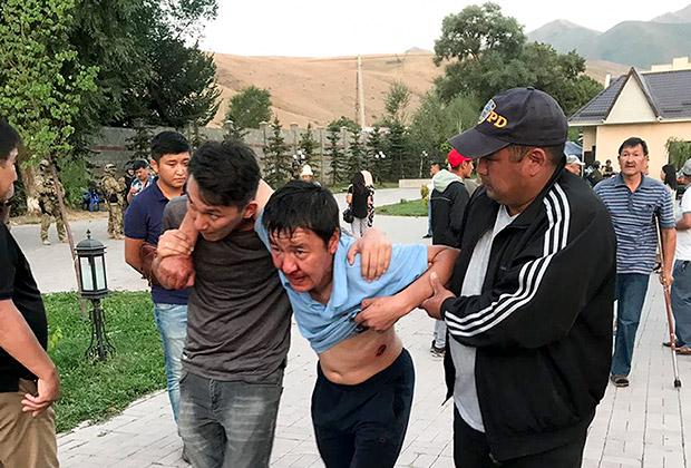 Люди выводят пострадавшего при стрельбе в Кой-Таше