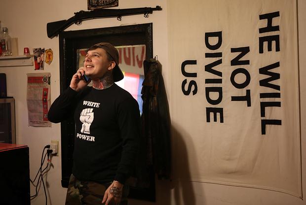 На флаге рядом с Каролло написано: «Ему нас не расколоть». Флаг, скорее всего, добыт в качестве трофея во время уличных боев с антифашистами, которые обвиняют президента Дональда Трампа в попытке расколоть общество с помощью расистской риторики. Надпись на футболке: «Белая сила».