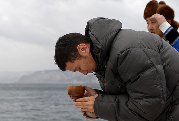 Ученик шамана в ходе обряда на улучшение погоды на озере Байкал