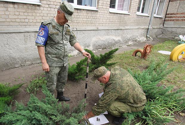 Представители ДНР из совместного центра по контролю и координации режима прекращения огня (СЦКК) в Донбассе осматривают осколки от артиллерийских снарядов после обстрела ночью 25 июня