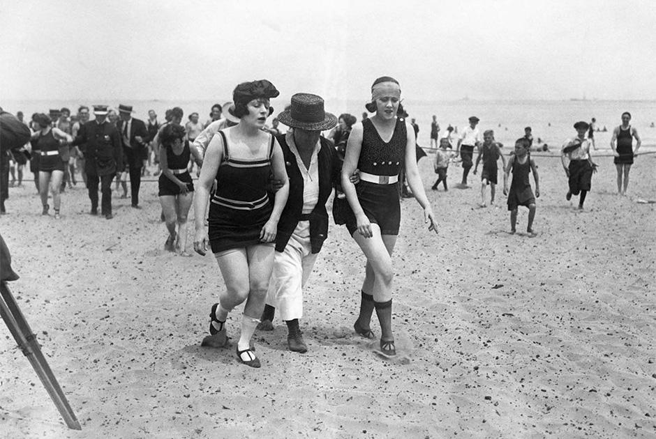 Полицейский ведет задержанных за слишком короткие купальники девушек во время одного из рейдов по пляжам США