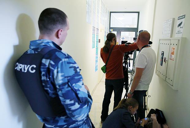 Охранник и журналисты у офиса РИА Новости— Украина в Киеве, где СБУ проводит обыски, 15 мая 2018 года