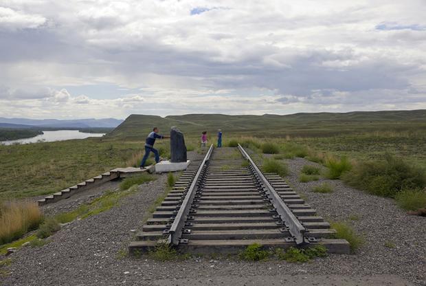 Закладной камень железнодорожного вокзала и символическое первое звено железной дороги Кызыл — Курагино в местечке Кундустуг (в русскоязычном обиходе — Бобры) близ Кызыла; слева виден Енисей. В Туве никогда не было железных дорог.  <br><br> Проект железнодорожной магистрали от Тувы до Транссиба через Саянские горы федеральное правительство утвердило еще в 2007 году, но, несмотря на регулярные заверения в скором начале строительства, он остается на бумаге из-за сомнений в его рентабельности. Из Тувы по железной дороге можно вывозить только уголь, но его здесь не так много, чтобы проект окупился, а большого пассажиропотока из Тувы в остальную Россию тоже нет.