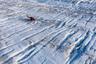 Вертолет ученых стоит на льду, пока исследователи устанавливают радар и GPS-антенны.