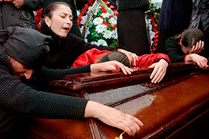 BESLAN, RUSSIA - SEPTEMBER 6:  Family and friends of those killed in the school hostage crisis cry over the coffin of a loved one during a mass funeral in the rain September 6, 2004 in Beslan, southern Russia. More than 350 people died after Chechen militant hostage-takers and Russian forces began a firefight that ended violently for more than 1200 held captive inside the school for three days. (Photo by Scott Peterson/Getty Images)