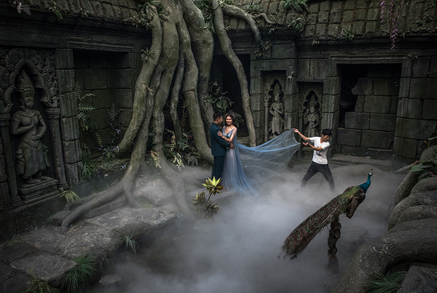 Самые состоятельные пары снимаются на фоне Эйфелевой башни в Париже и возле других достопримечательностей в разных странах мира. Те, кто не может позволить себе такого удовольствия, ищут студии с подходящими декорациями. У китайских свадебных фотографов найдется и поддельный Париж, и даже фальшивый кхмерский храм Ангкор-Ват, как на этом кадре.