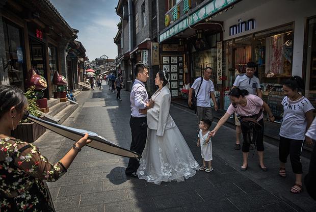 Еще один популярный задник для свадебной фотографии — китайская экзотика. Некоторые пары позируют на фоне хутунов — тесных средневековых трущоб, которые сохранились в некоторых городах. Хотя эти места считаются памятником старины, там до сих пор живут люди. Им приходится терпеть нашествие женихов и невест, желающих сняться на фоне их ветхих жилищ.
