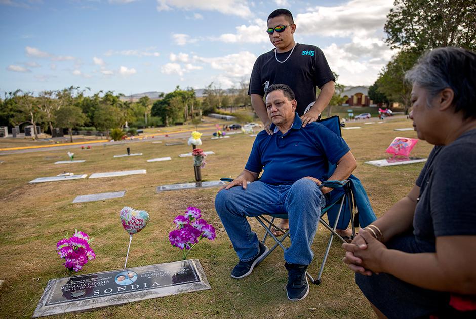 57-летний Роланд Сондиа вместе с сыном и женой на могиле матери. Она умерла до того, как он рассказал ей о произошедшем