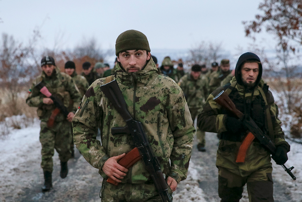 """Pro-Russian separatists from the Chechen """"Death"""" battalion walk during a training exercise in the territory controlled by the self-proclaimed Donetsk People's Republic, eastern Ukraine, December 8, 2014. Chanting """"Allahu Akbar"""" (God is greatest), dozens of armed men in camouflage uniforms from Russia's republic of Chechnya train in snow in a camp in the rebel-held east Ukraine. They say their """"Death"""" unit fighting Ukrainian forces has 300 people, mostly former state security troops in the mainly-Muslim region where Moscow waged two wars against Islamic insurgents and which is now run by a Kremlin-backed strongman."""